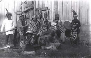 A group of Tlingit men outside a clan house.